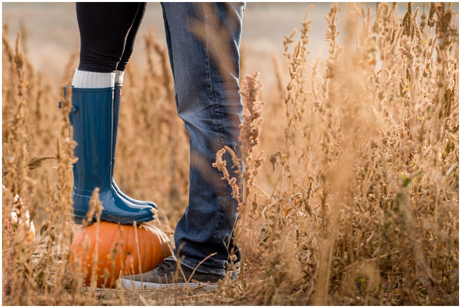 Kamloops engagement photographer hunter boots standing on a pumpkin fall love session