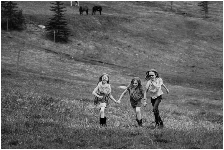 Kamloops editorial family photographer sisters running up the mountianside black and whtie