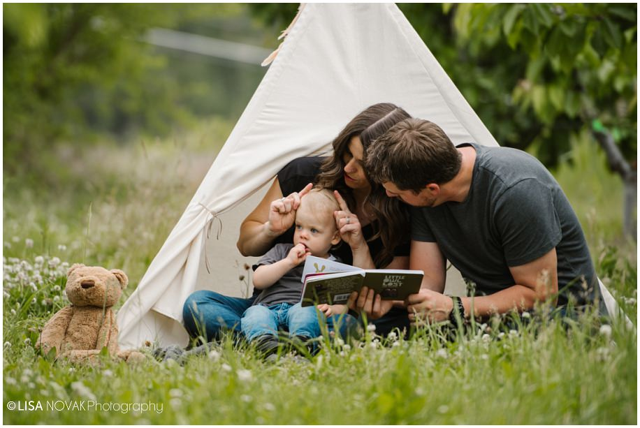 Okanagan lifestyle family session apple orchard toddler Summerland photographer teepee grass reading toddler