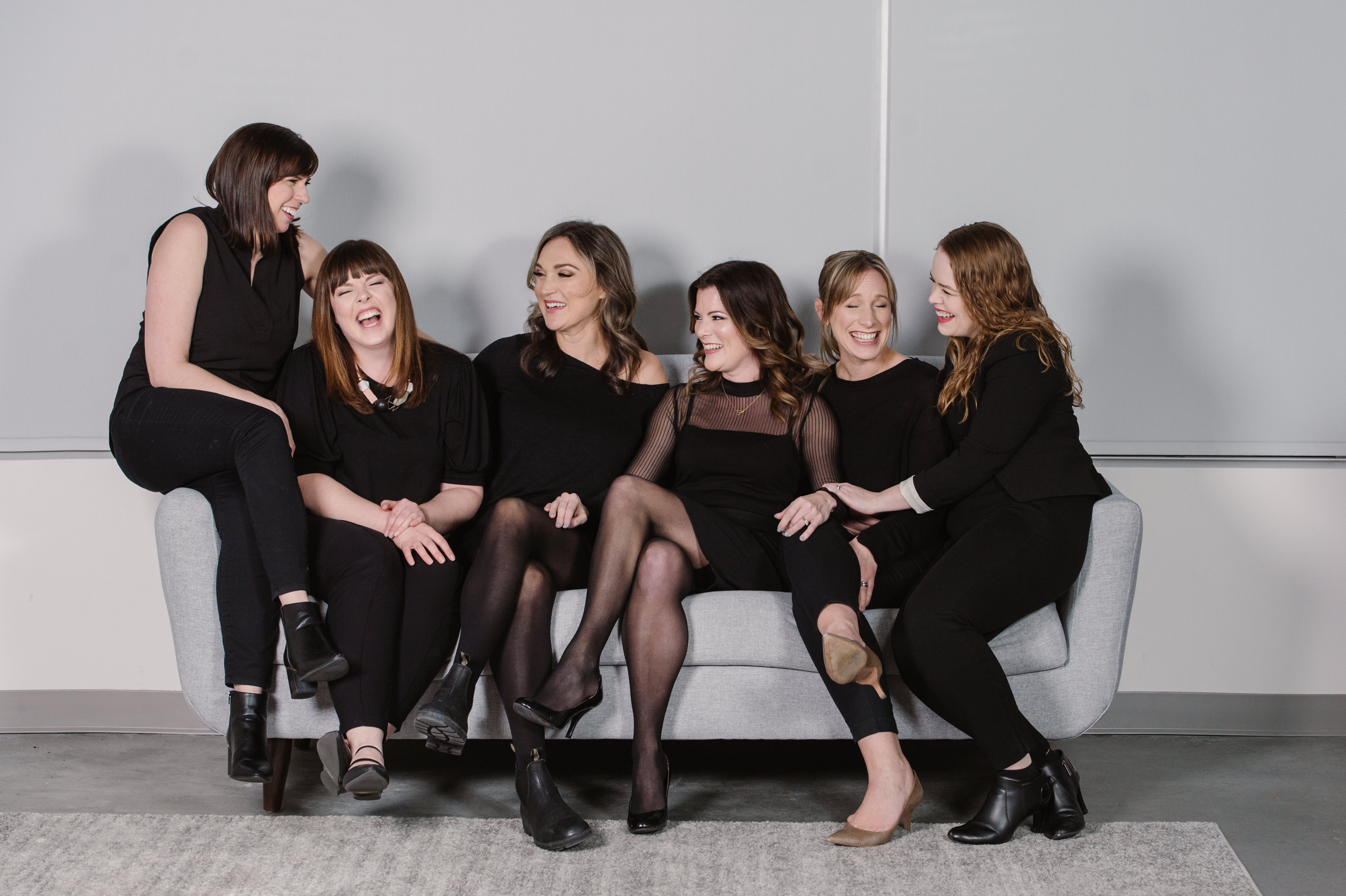 Fun indoor corporate team photo of a group of laughing women Kamloops headshot photographer